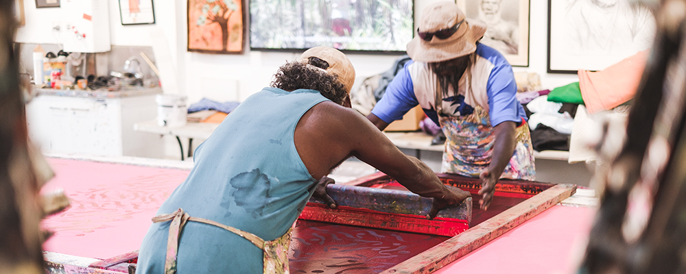Aboriginal screen printers working on a piece